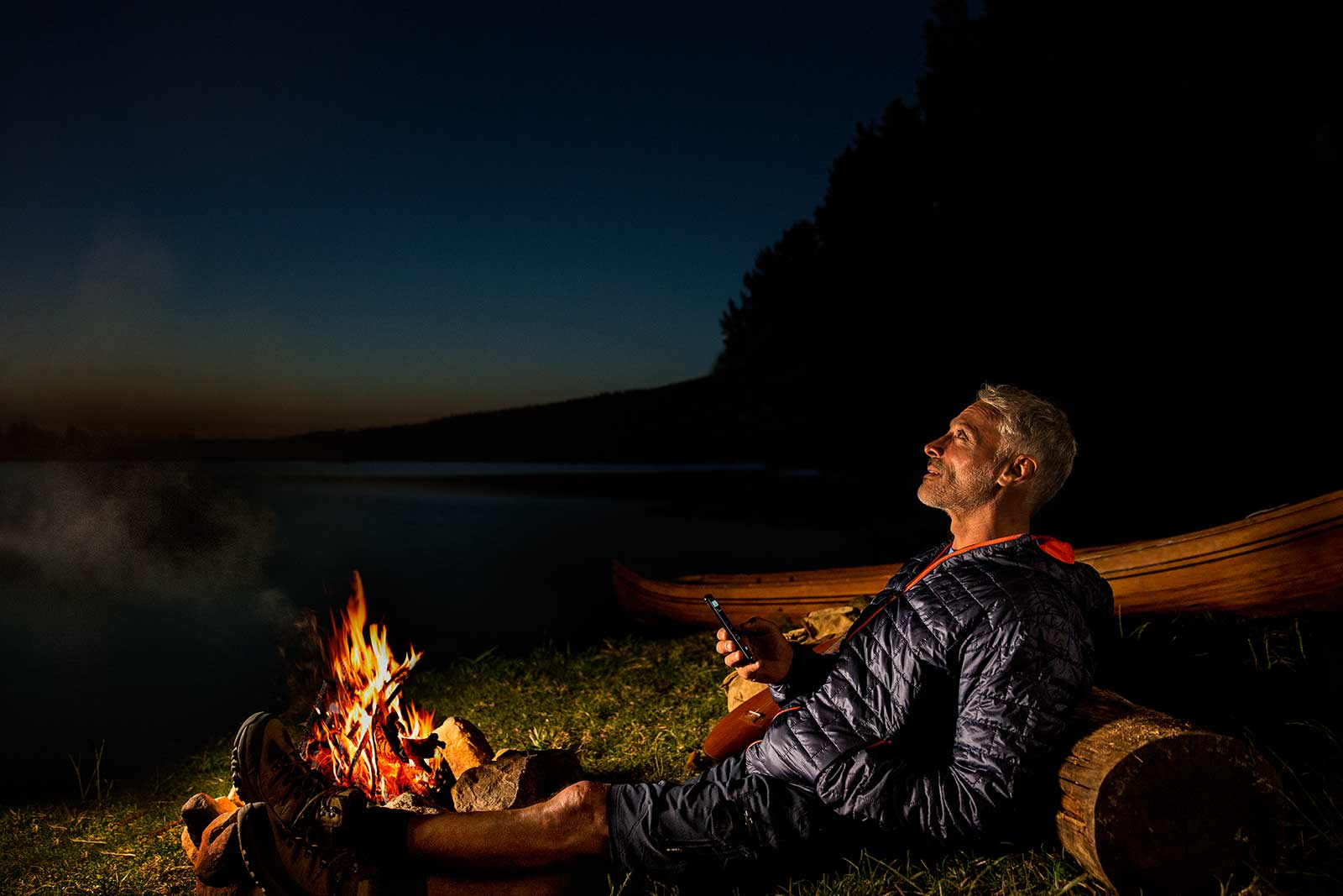 Man sitting in front of bonfire listening to soft level noises through his EVOKE hearings aids